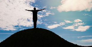 Silhouette man open arms. Standing alone on hill Stock Image