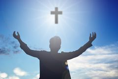 Silhouette of man. Open hands and cross stock photos