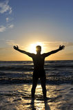 Silhouette of a man with outstretched arms. On the beach Stock Photos