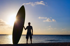Silhouette of man with paddle board. Silhouette of man holding paddle board on a beach at sunset Stock Photos