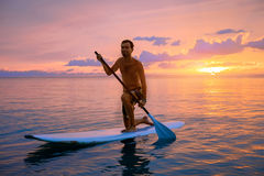 Silhouette of man paddleboarding at sunset Royalty Free Stock Photo