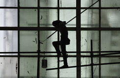 Silhouette of man painting on green glass window wall with paint Stock Photo