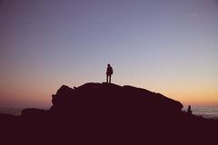 Silhouette of Man on Peak of the Mountain during Sunset Royalty Free Stock Image