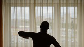 Silhouette of a man performing exercise indoors. In the background city street behind window curtains. Men warming up do stock video