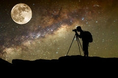 Silhouette  of man photography take a photo of Milky Way galaxy. And full moon on dark night at thailand Royalty Free Stock Photography