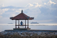 Silhouette of the man on the pier and ships at the horizon. Man is sitting on the pier Stock Image