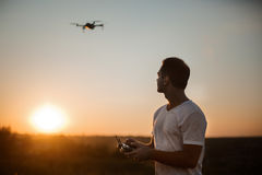 Silhouette of a man piloting drone in the air with a remote controller in his hands on sunset. Pilot takes aerial photos Stock Photo