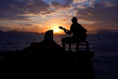 Free Silhouette Man Playing A Guitar On The Boat With Blue Sky Sunrise Stock Image - 99654631