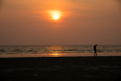 Silhouette man playing on beach. In the sea on sunset background Royalty Free Stock Photos