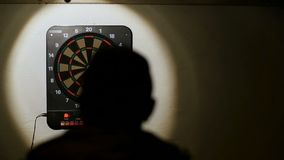 Silhouette man playing a game of darts, focus on target slow motion FAIL stock video
