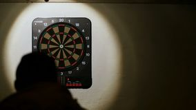 Silhouette man playing a game of darts, focus on target slow motion FAIL stock video footage