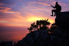 Silhouette man playing a guitar on the mountain stock photography