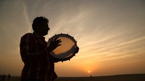 Silhouette of man plays the drum in sun set stock video footage