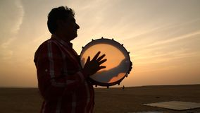 Silhouette of man plays the drum in sun set stock video