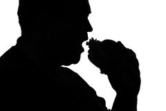 Silhouette of a man plump biting fast food Royalty Free Stock Image