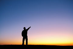Silhouette of man pointing finger in air at sunset Royalty Free Stock Images