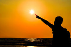 Silhouette of a man pointing towards the sun Royalty Free Stock Images
