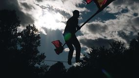 The silhouette of a man with a pole jumping on a rope above the ground. Cool tricks against the sky stock footage