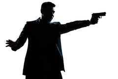 Silhouette man portrait with gun aiming. One caucasian man with gun aiming portrait silhouette in studio isolated white background Royalty Free Stock Images