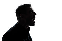 Silhouette man portrait profile screaming angry. One caucasian man portrait silhouette profile screaming angry in studio isolated white background Stock Photo