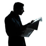 Silhouette man portrait reading newspaper Stock Photos
