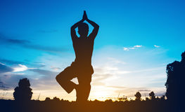 Silhouette of man practicing yoga Stock Photo