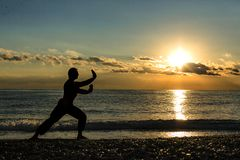Silhouette of a man practises wing chun on the beach stock photo