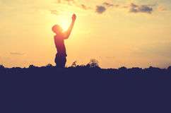 Silhouette of man pray with sunset background Stock Image