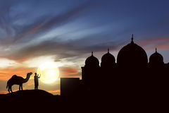 Silhouette man praying with camel outside the mosque Royalty Free Stock Images