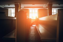 Silhouette of man praying in church in sunset light. Toned stock photography