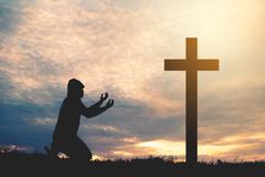 Silhouette man praying with cross. During sky sunset Stock Image