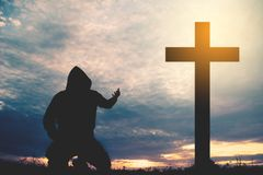 Silhouette man praying with cross. During sky sunset Stock Photo