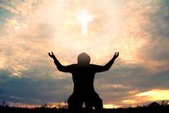 Silhouette man praying with cross. During sky sunset Stock Photos
