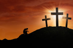 Hope of the Cross. Silhouette of a man is praying for hope by the Cross under sunset background Royalty Free Stock Image