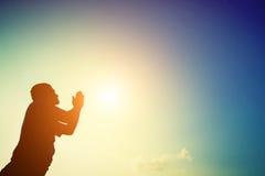 Silhouette of man praying at sunrise. Stock Photography
