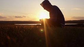 Silhouette of a man praying at sunset concept of religion stock video footage