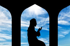 Silhouette of man praying at the Town Hall Stock Images