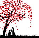 Silhouette of a man presenting a heart on his knee to a beautiful woman under a love tree in the spring season Royalty Free Stock Images