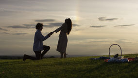 Silhouette man proposes at sunset to his girlfriend Stock Photo