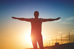 Silhouette of man with raised arms at sunset.  Royalty Free Stock Photography