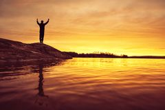 Joyful person during a sunset at a lake. Silhouette of a man with raised arms. During a warm and atmospheric sunset Stock Photo