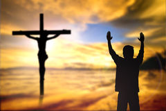 Silhouette of man with raised hands over blur cross concept for Royalty Free Stock Photography