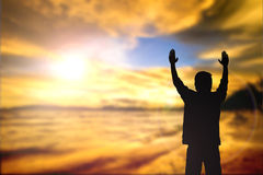 Silhouette of man with raised hands over blur cross concept for Stock Photography