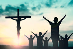 Silhouette of man with raised hands over blur cross concept for Royalty Free Stock Photo