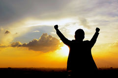 Silhouette of a man raising his arms in twilight sky background Stock Images