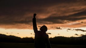 Man raising his fist against sunset sky. Silhouette of a man raising his fist against sunset sky with clouds Stock Photos