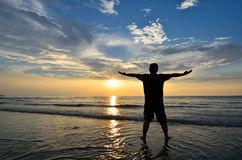 Silhouette of Man Raising His Hands Stock Photo