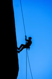 Silhouette of Man Rappelling Stock Image
