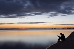 Silhouette of man reading near to lake at sunset.  Royalty Free Stock Image
