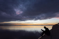Silhouette of man reading near to lake at sunset Stock Photography